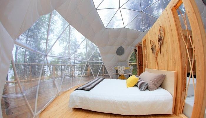 Возле кровати, расположенной на нижнем ярусе, организовали шкафы для хранения вещей (Domes Charlevoix, Канада). | Фото: jolijolidesign.com.