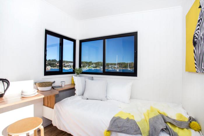 Угловое окно обеспечивает спальное место и рабочий кабинет дневным светом. | Фото: designerecotinyhomes.com.au.