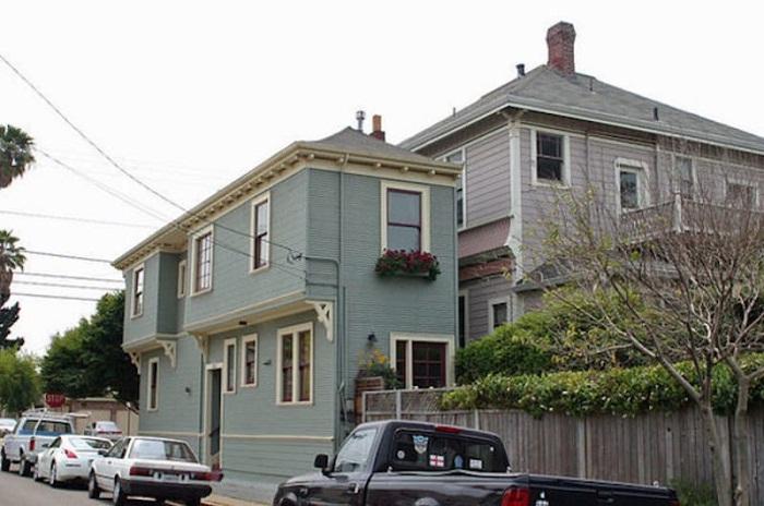 Узкий дом, нависающий над тротуаром, построил обиженный наследник.