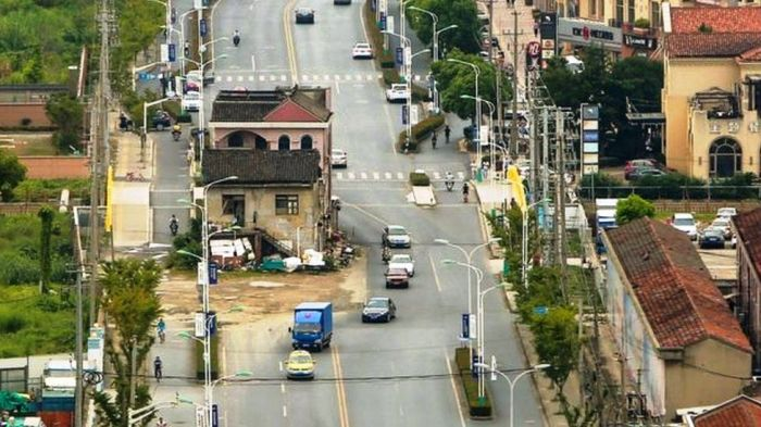 Еще одна шанхайская улица сужается до двух полос из-за упрямства владельцев дома, которые так и живут посреди шума и гари. | Фото: bbc.com.
