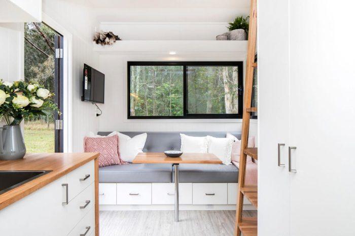 В обеденной и гостиной зоне установлен специальный диван с ящиками для хранения вещей и оригинальный стол. | Фото: tinyliving.com.
