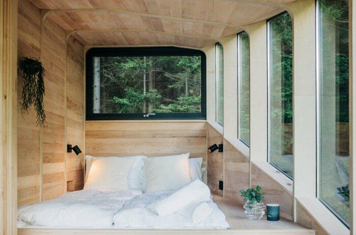 В основной спальне, помимо двуспальной кровати, созданы встроенные шкафы, которые замаскировали под деревянную обшивку (Woodnest, Норвегия). | Фото: dwell.com.