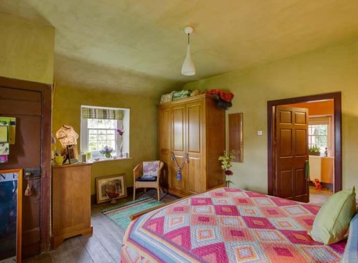 Добротная винтажная мебель и колоритный текстиль украшают спальную комнату. | Фото: scotsman.com.