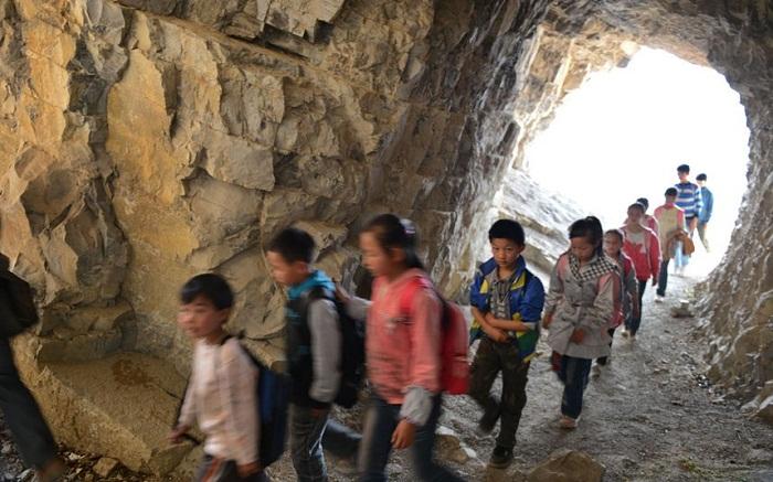 Детям приходится преодолевать не только обрыв, но и тоннель.