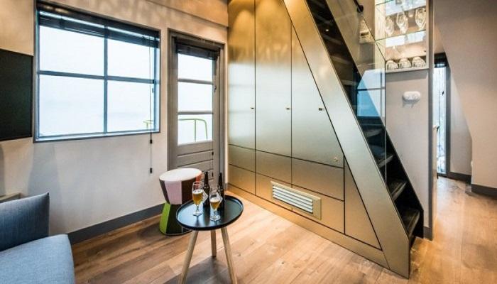 Стальная лестница, идущая на второй этаж апартаментов, служит местом хранения для вещей (Yays Crane Apartment, Амстердам). | Фото: interestingengineering.com.