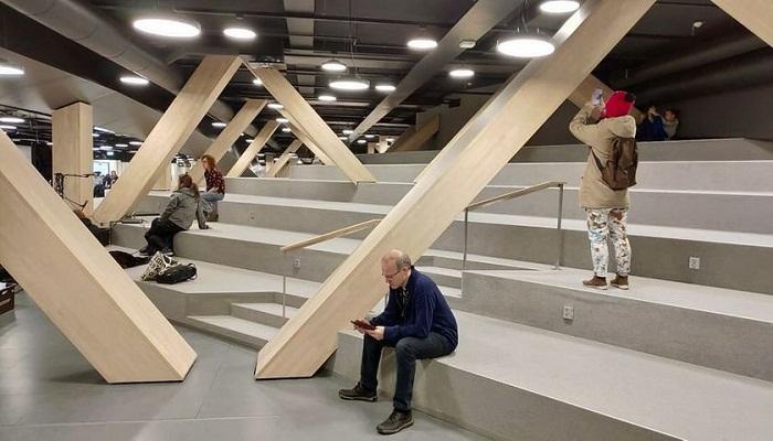 Большой амфитеатр с деревянными опорами служит местом для чтения, общения и просто отдыха (Центральная библиотека Oodi, Хельсинки). | Фото: strelkamag.com.