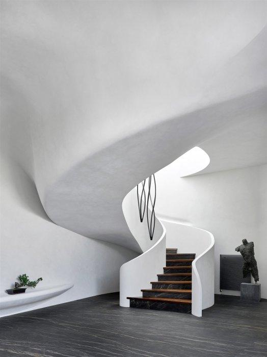 Оригинальная лестница, ведущая на второй этаж, повторяет те же органичные линии, что все строение в целом («Дом в ландшафте», Подмосковье). | Фото: arquitecturaydiseno.es.
