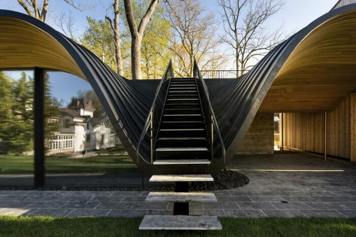 Наружную стальную лестницу установили в нижней части волнообразного контура крыши (Fold House, Гамильтон). | Фото: world-architects.com.