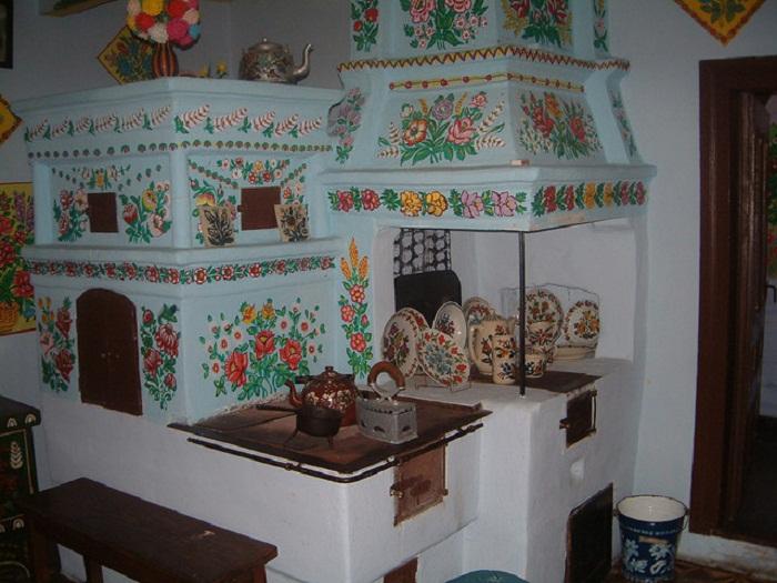 Оформление русской печки в стиле «а-ля рюс». Украшена народным орнаментом и элементами старинной домашней утвари.