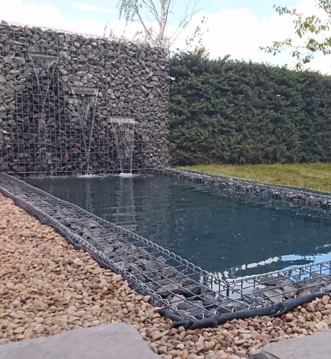 Габион в качестве отделки бортиков бассейна и каменные стены с водопадами облагородят зону отдыха у воды. | Фото: topgabion.ru.