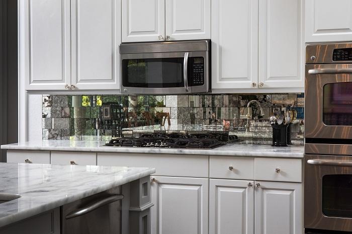 Зеркальный фартук с эффектом потертости тоже поможет придать глубину пространству.