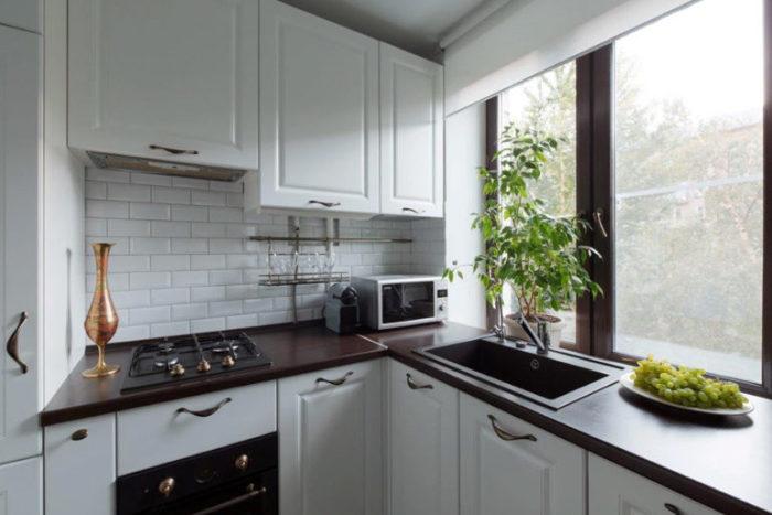 Мойка вместо подоконника поможет сэкономить место. | Фото: kitchendecorium.ru.