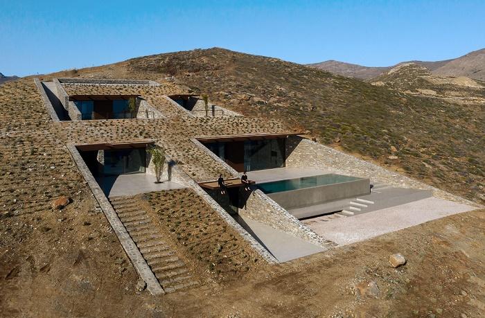 Фасад резиденции и прилегающая к ней территория засажены невысокими кустарниками (Ncaved House, о-в Серифос). | Фото: thegreekfoundation.com.