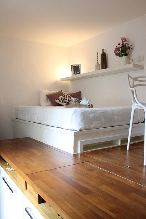 Огромная кровать с белоснежным покрывалом и яркими подушками, полка для декоративных вещиц — добавляют утонченности и шарма интерьеру квартиры.