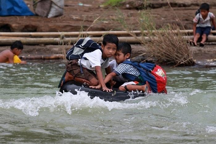 Дети в школу добираются по бурлящей реке.