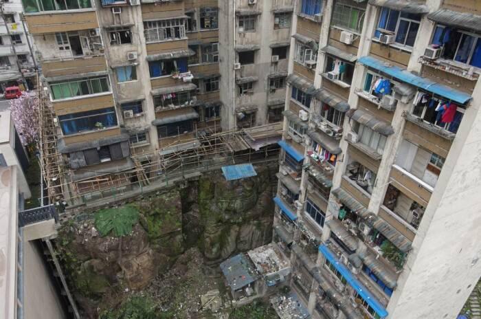 Даже жители нижних этажей, рядом стоящей высотки, не знали, что часть соседского фундамента состоит не только из обычного камня (Большой Будда Наньпиня, Китай). | Фото: ground.news.
