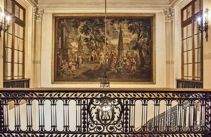 Огромные картины и кованные перила украшают лестничные пролеты.