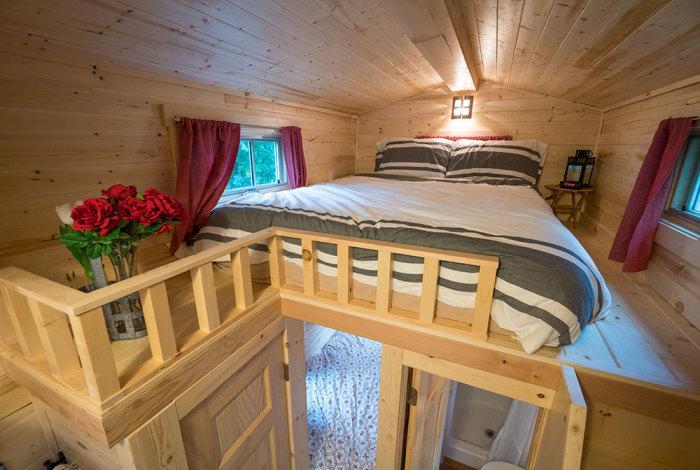 Благодаря мансардной надстройке спальню расположили на втором ярусе. | Фото: tumbleweedhouses.com.