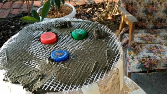 Если использовали армированную сетку, то заранее нужно вырезать отверстия и поместить в них крышки от пластиковых бутылок. | Фото: © Марина Фокина.