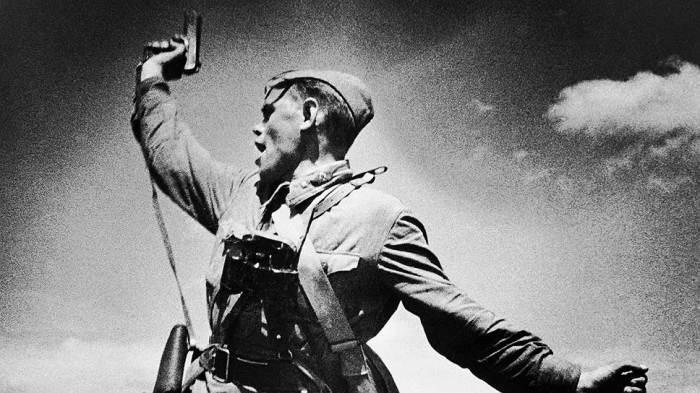 Солдат Красной армии Алексей Ерёменко с пистолетом ТТ призывает бойцов в атаку.
