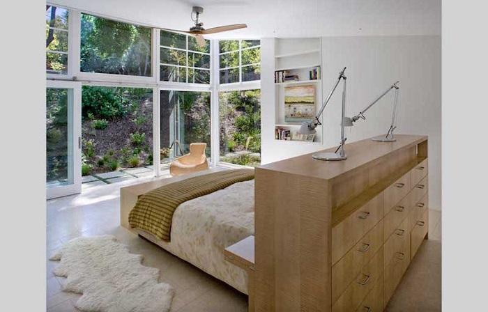 Многофункциональная спинка кровати одновременно подойдет для зонирования и хранения вещей. / Фото: rehouz.info
