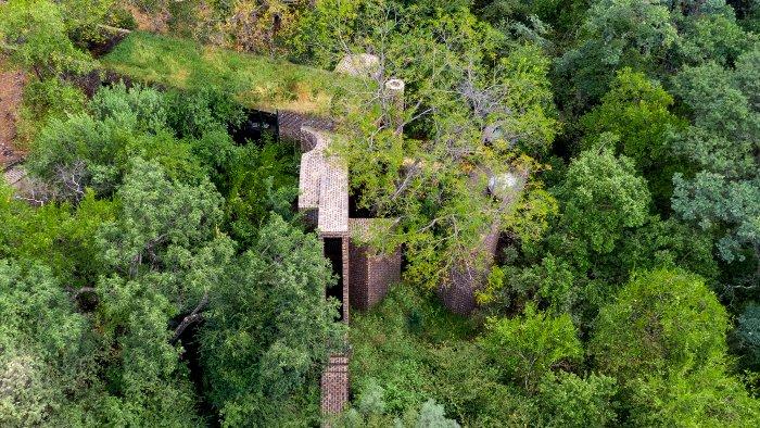 Африканский дом, уникальным образом вписанный в ландшафт. /Фото: arquine.com