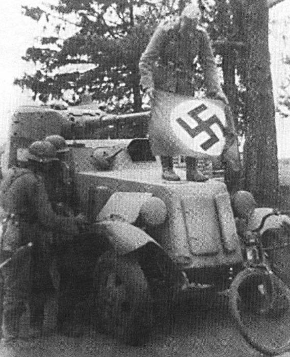 Немцы закрепляют свастику на трофейном бронеавтомобиле БА-10, чтобы уберечься от авианалета своих. /Фото: newsvo.ru