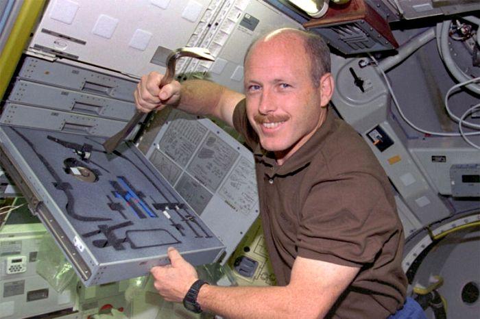 Астронавт Кеннет Боуэрсокс с аншпугом на борту шаттла в 1995 году. /Фото: teoti.com