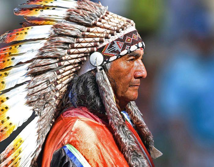 Представитель племени сиу в аутентичной одежде с венцом из перьев на голове. /Фото: irinatraveling.com