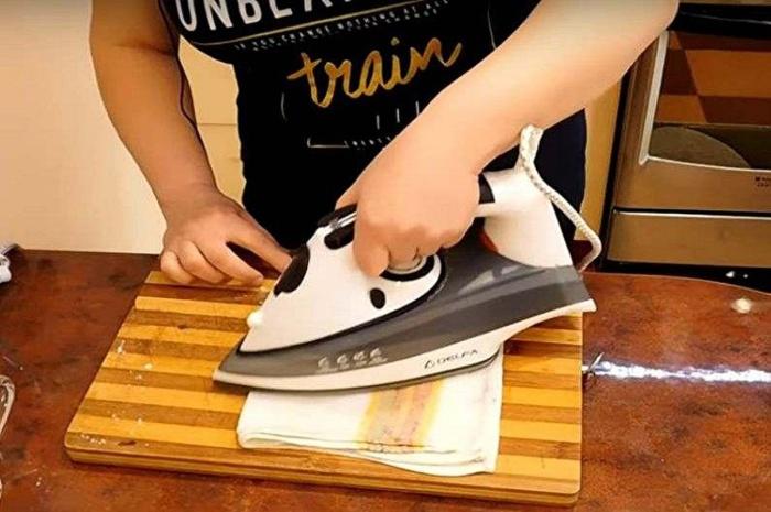 На процесс глажки уходит около двух-трех минут, этого времени достаточно, чтобы нагар с подошвы остался на полотенце / Фото: