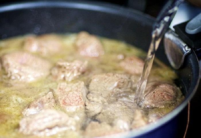 Обжаренное мясо заливают бульоном и тушат около часа / Фото: kulray.ru