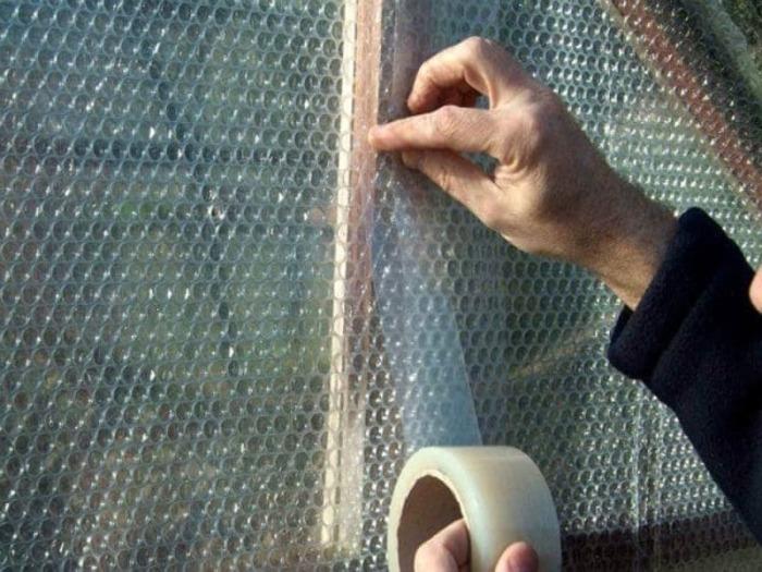 Пленку необходимо зафиксировать на окне скотчем, желательно двусторонним / Фото: sad-ogorod.in.ua