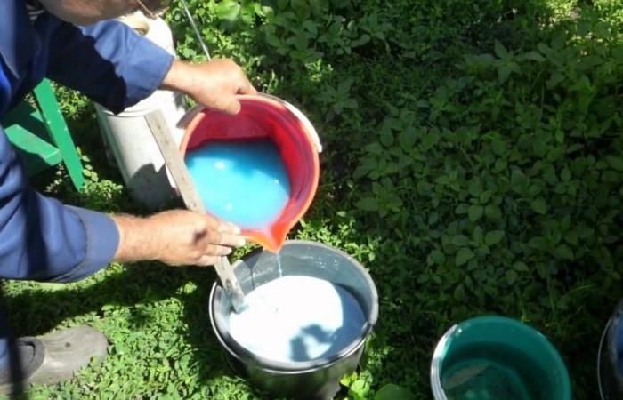 Раствор медного купороса нужно вливать в емкость с известью / Фото: newogorod.ru