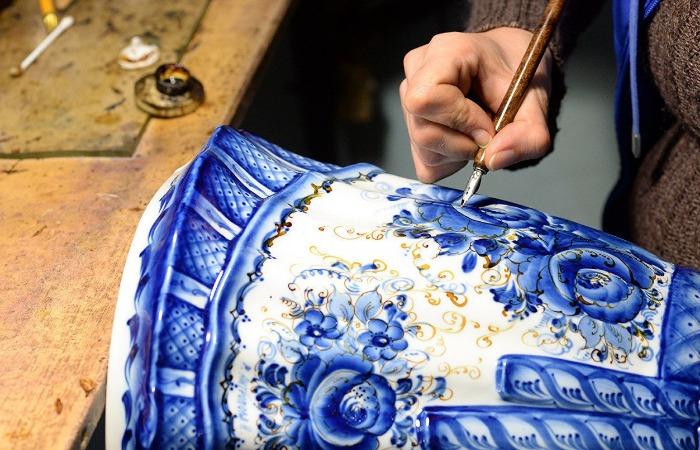 Мастера расписывают изделия синими красками и украшают золотом по контуру / Фото: cdn.fishki.net