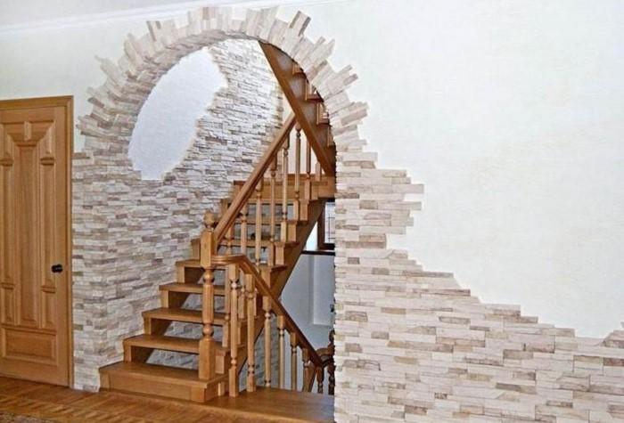 Искусственный камень выкладывается двумя способами: боковой полосой вокруг арочного проема или по всей стене / Фото: archidea.com.ua