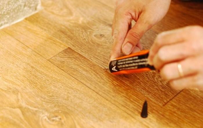 Прореху в напольном покрытии можно замаскировать с помощью клея и спецсредств / Фото: remboo.ru