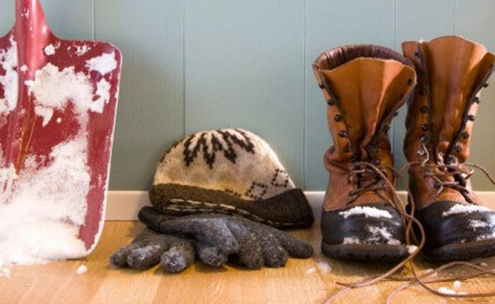 Снег на обуви начинает оттаивать в теплом коридоре, создавая лужи грязи