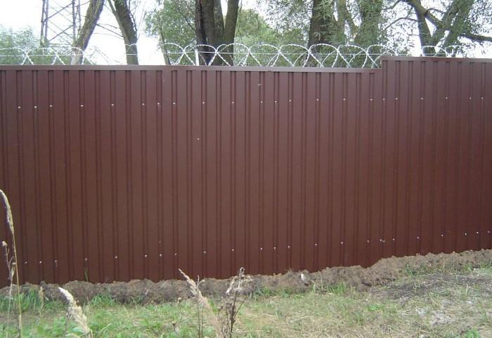 Сделайте насыпь по обе стороны забора вплоть до ограды, немного утрамбовывая почву / Фото: хорошим-людям.рф