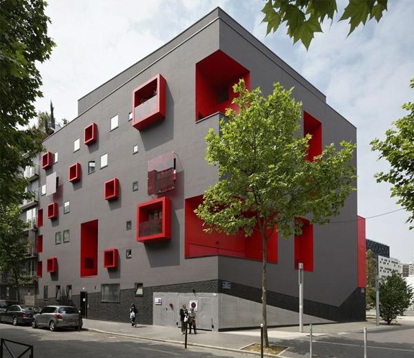 Стена дома с красными оконными проемами и нишами.